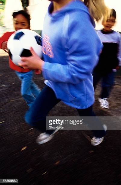 Side profile of a young girls (8-10) one who is running with a football (blurred)