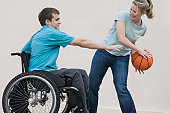 Disabled man sitting in a wheelchair and playing basketball with a woman