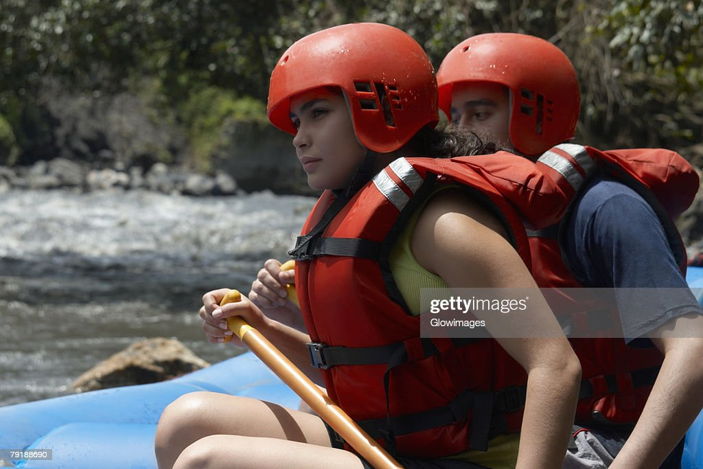 Side profile of a young man and a young woman rafting in a river : Foto de stock