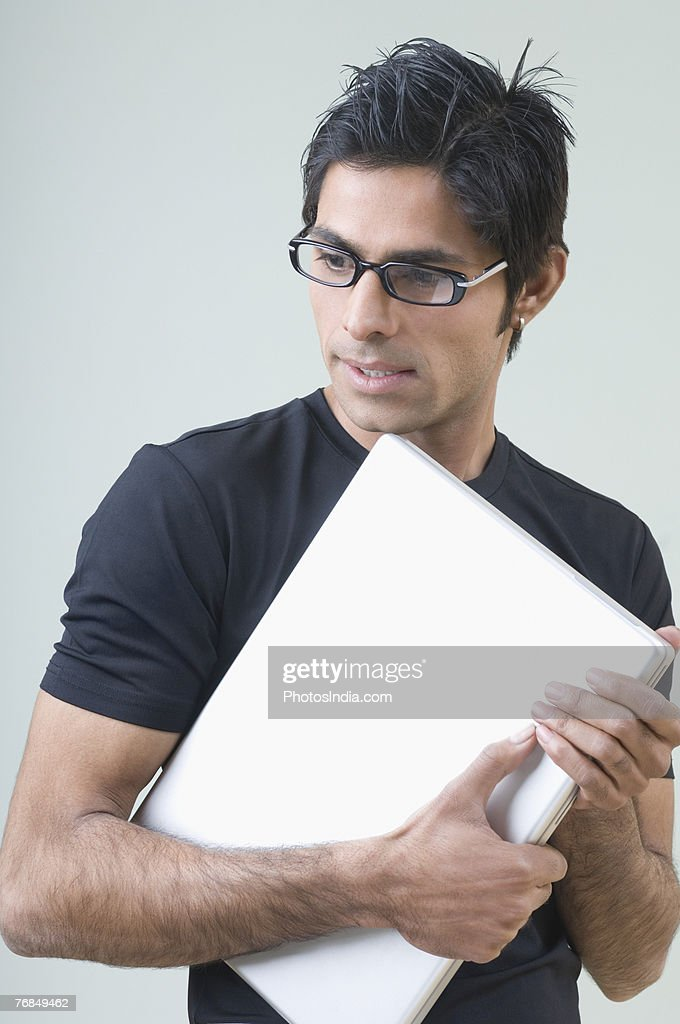 side profile of a young man holding a laptop stock photo. Black Bedroom Furniture Sets. Home Design Ideas