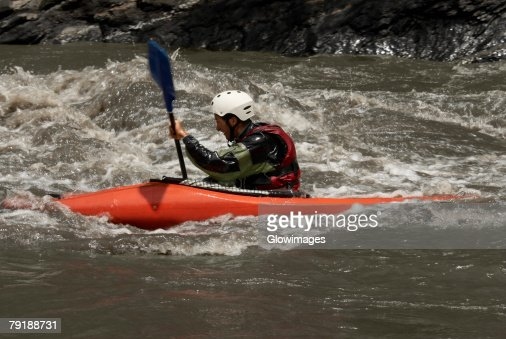 Side profile of a young man kayaking in a river : Foto de stock