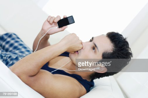 Side profile of a young man listening to an MP3 player : Stock Photo