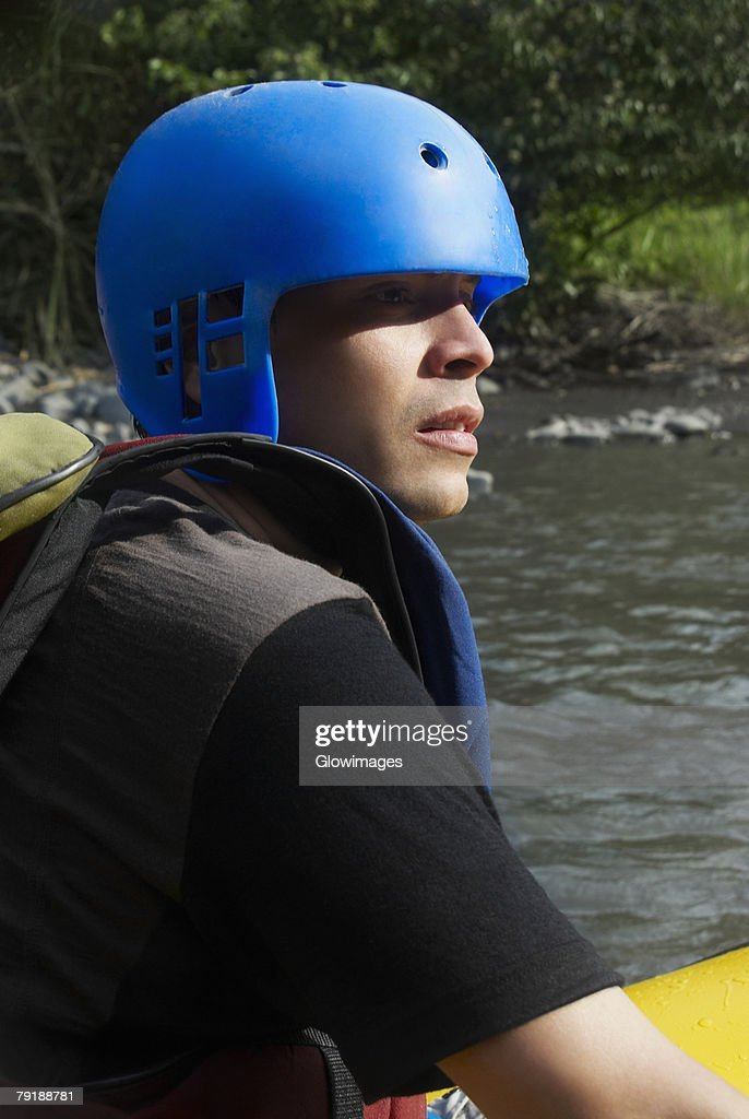 Side profile of a young man rafting in a river : Foto de stock