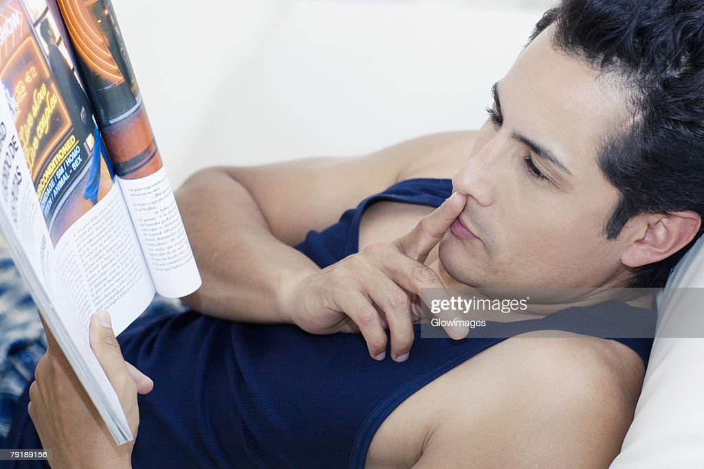 Side profile of a young man reading a magazine with his finger on his lips : Foto de stock