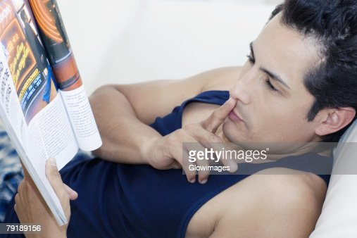 Side profile of a young man reading a magazine with his finger on his lips : Stock Photo
