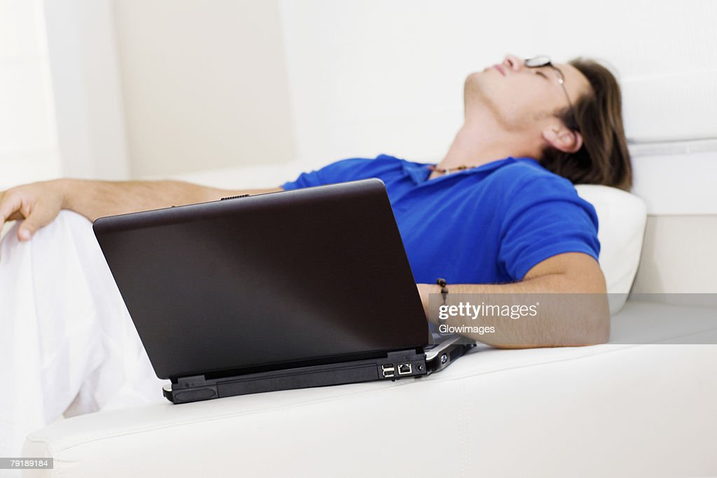 Side profile of a young man reclining on a couch : Foto de stock
