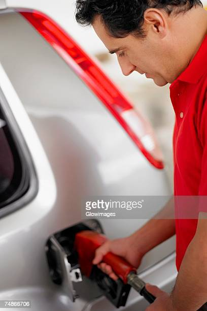 Side profile of a young man refueling a car