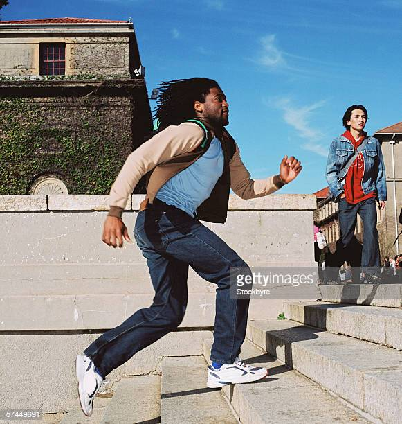 side profile of a young man running up a flight of stairs