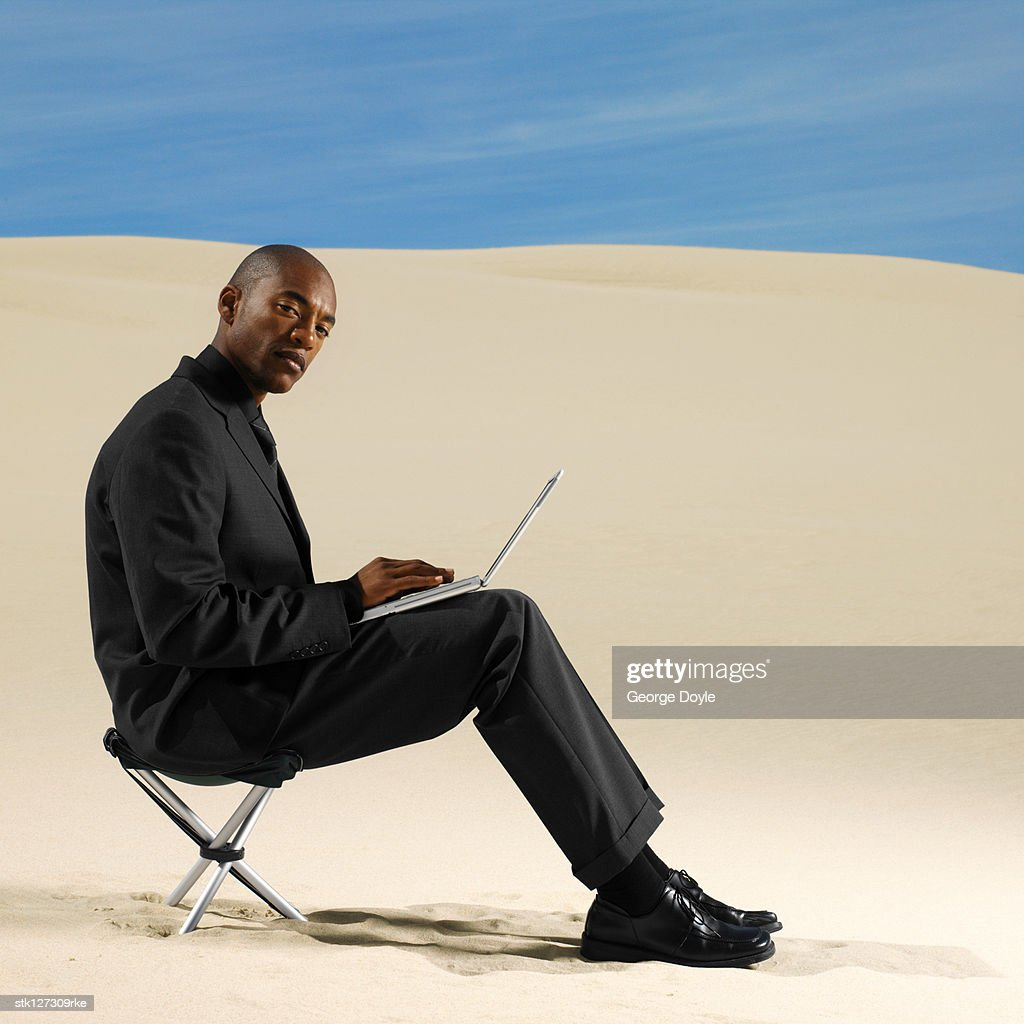 Man sitting in chair side - Side Profile Of A Young Man Sitting On A Chair Operating A Laptop Stock Photo