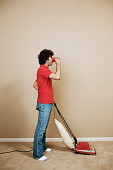 Side profile of a young man using a vacuum cleaner