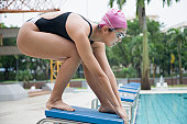 Side profile of a young woman bending on a starting block