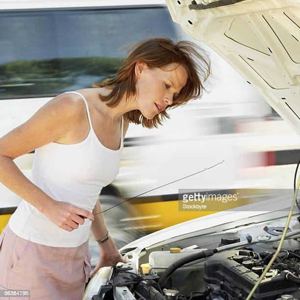 side profile of a young woman checking the oil level of a car