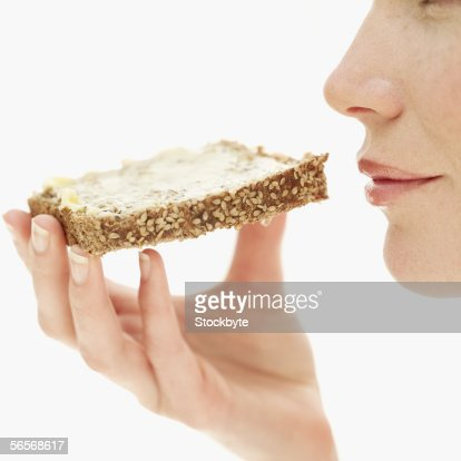 side profile of a young woman holding a piece of sesame seed toast