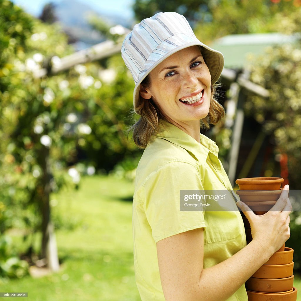 side profile of a young woman holding a stack of flowerpots
