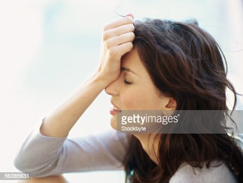 side profile of a young woman holding her head in her hand : Stock Photo