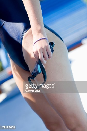 Side profile of a young woman holding swimming goggles at the poolside : Foto de stock