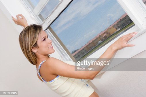 Side profile of a young woman looking through a window and smiling : Foto de stock