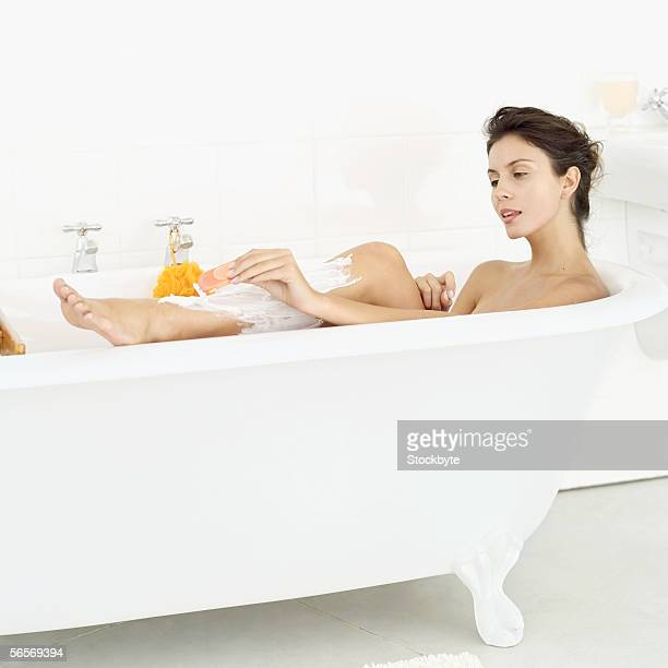 side profile of a young woman lying in a bathtub shaving her leg