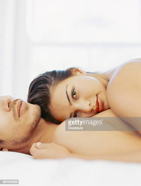 side profile of a young woman lying on top of a young man
