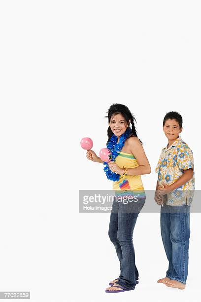 Side profile of a young woman playing maracas and a boy playing ukulele
