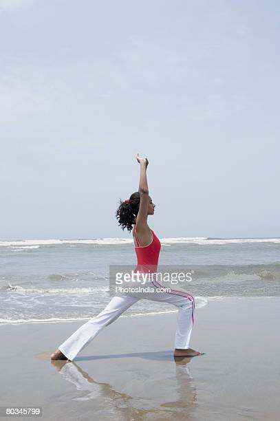 Side profile of a young woman practicing yoga on the beach