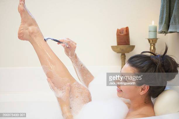 Side profile of a young woman shaving her legs in a bathtub