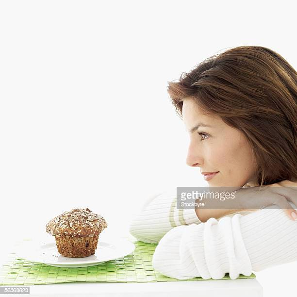 side profile of a young woman sitting in front of a muffin
