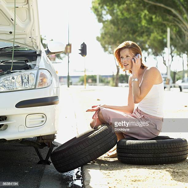 side profile of a young woman sitting on a tire talking on a mobile phone