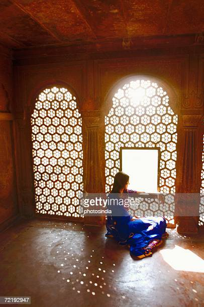 Side profile of a young woman sitting on the floor of a mausoleum, Taj Mahal, Agra, Uttar Pradesh, India