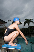 Side profile of a young woman squatting on a starting block