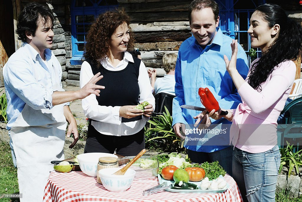 Side profile of a young woman standing with a mature man and a mid adult couple near a table : Foto de stock