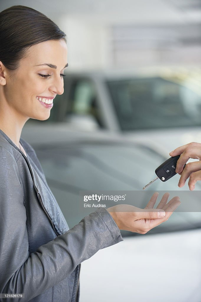 side profile of a young woman taking car key in showroom stock foto getty images. Black Bedroom Furniture Sets. Home Design Ideas