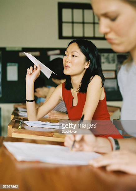 Side profile of a young woman throwing a paper plane in a classroom with other students around her
