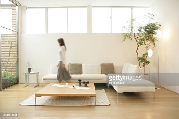 Side profile of a young woman walking in the living room