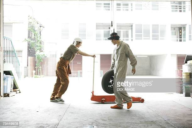 Side profile of an auto mechanic holding a tire with a mechanic pushing a car jack