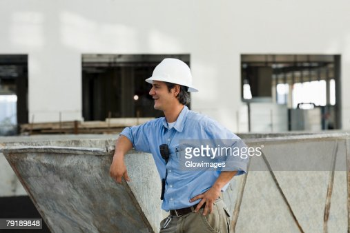 Side profile of an engineer leaning against an industrial equipment : Stock Photo