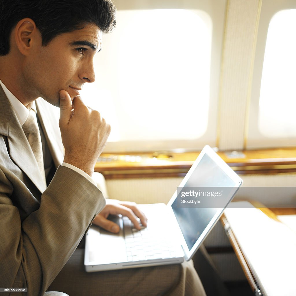 side profile of businessman using laptop in an airplane : Stock Photo