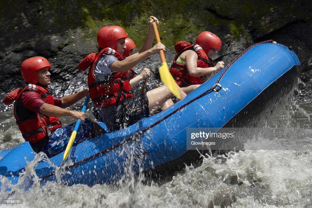 Side profile of five people rafting in a river : Foto de stock