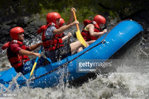 Side profile of five people rafting in a river : Foto de stock