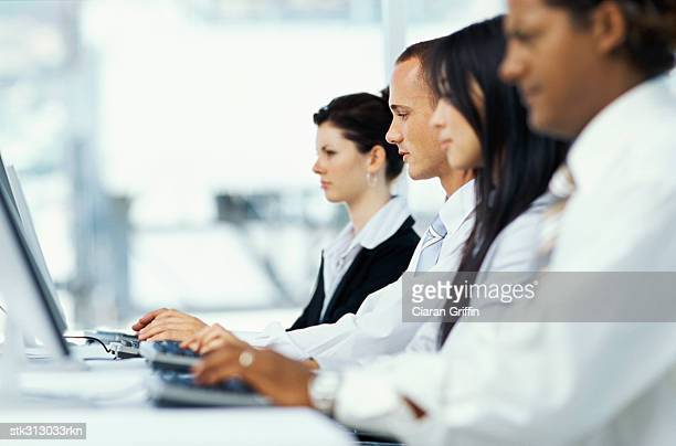 side profile of four business executives using computers in an office
