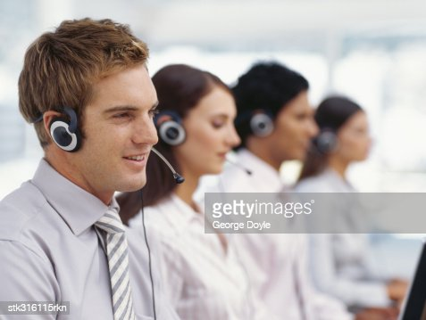 side profile of four business executives wearing headsets in an office : Stock Photo