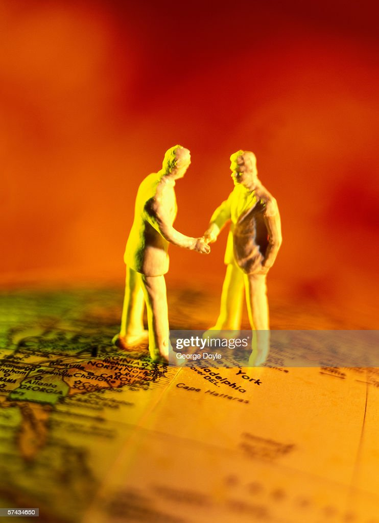 side profile of male figures shaking hands on a globe : Stock Photo