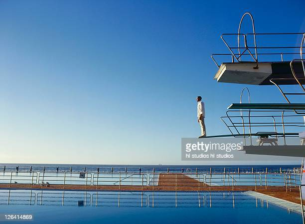 Side profile of man standing on diving board