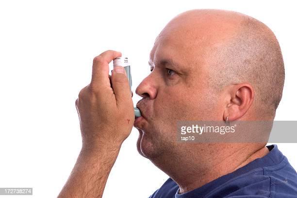 Side profile of man using asthma inhaler
