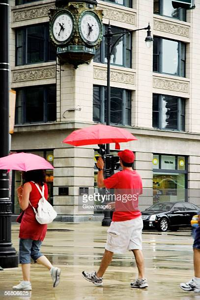 Side profile of pedestrians walking with umbrellas on a sidewalk, Chicago, Illinois, USA