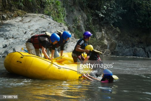 Side profile of three people pulling their friends on the raft : Foto de stock