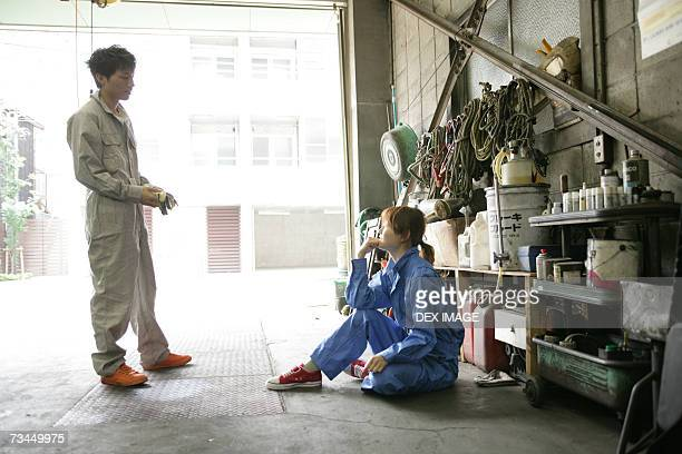 Side profile of two auto mechanics talking in an auto repair shop