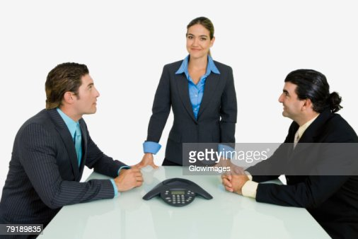 Side profile of two businessmen and a businesswoman in a conference room : Foto de stock