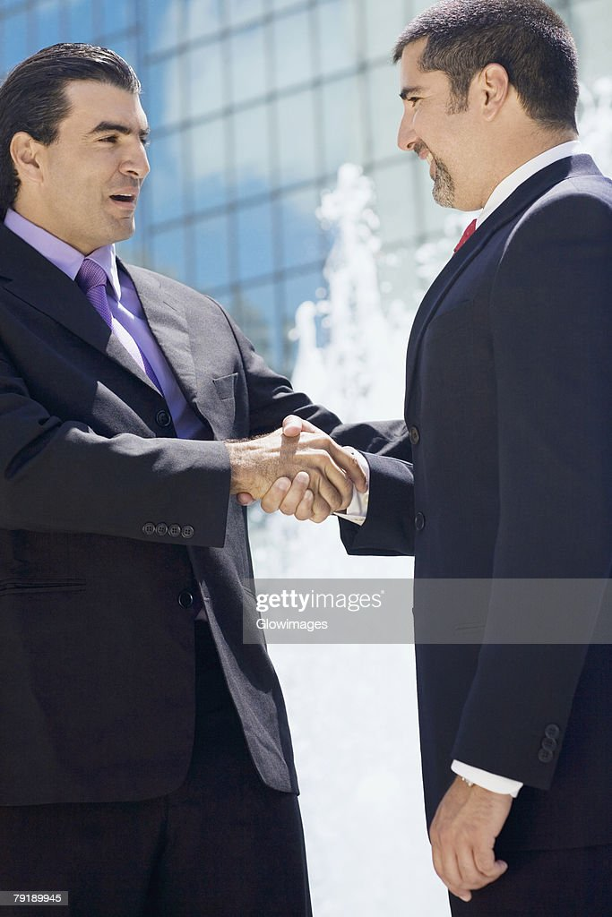Side profile of two businessmen shaking hands : Stock Photo