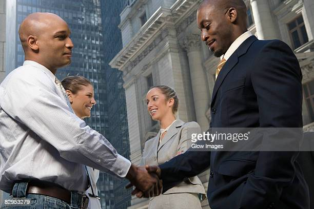 Side profile of two businessmen shaking hands with two businesswomen smiling